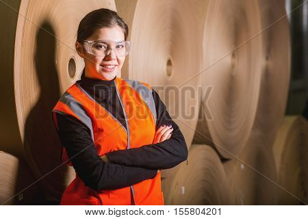 Paper mill factory female worker with giant paper rolls on the background