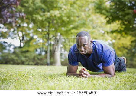 Fit Man Doing Plank Core Exercise In The Park
