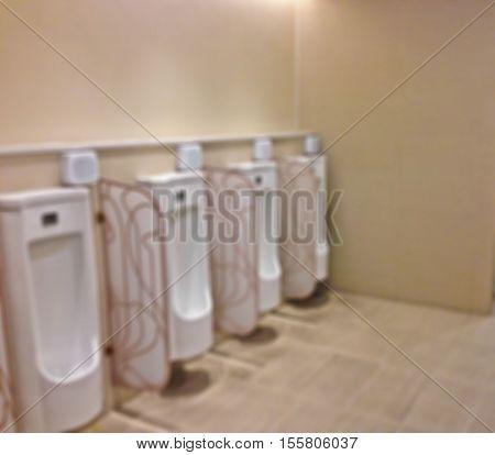 Abstract blur row of urinals men public toilet