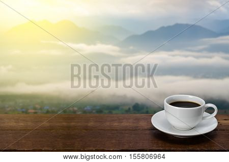 A Cup of coffee on a wooden table with mountain fog and sunflare blurred background in morning.