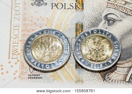 photograph taken close-up, which shows the Polish coin lying on the paper money. Zloty, a small depth of field