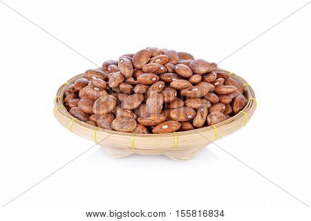 uncooked pinto beans in bamboo basket on white background