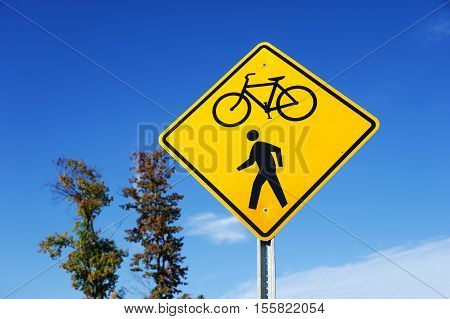 bicycle and pedestrian sign against blue sky