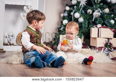 two brothers in anticipation of Christmas at the Christmas tree. Christmas decorations