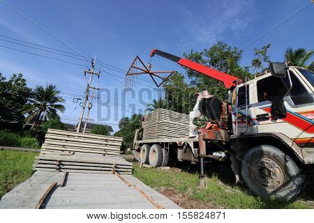 Worker controls of lifting crane for transporting concrete slabs