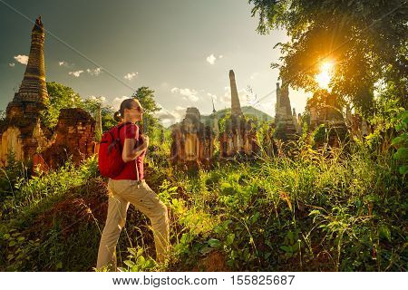 female traveler with backpack walking and looks at sunset among ancient Buddhist stupas of the temple complex In Dein Inle Lake. Mayanmar