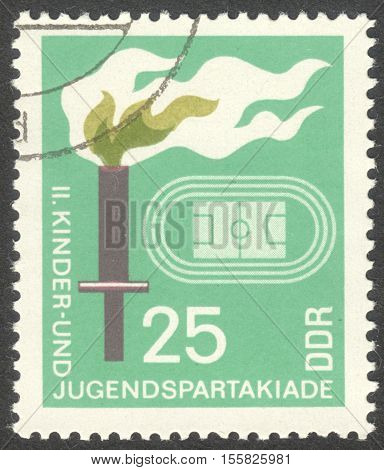 MOSCOW RUSSIA - CIRCA OCTOBER 2016: a post stamp printed in DDR shows a stadium and a torch the series