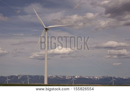 Close up of a wind turbine in a rural wind farm in Montana with the Judith Mountains in the background on a cloudy day.
