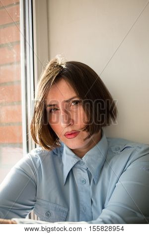 Strict woman with short hair caret in the blue shirt