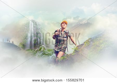 Young woman tourist with a backpack walking in the rain forest on background waterfall and mountains. Concept eco tourism hiking in the deep jungle.