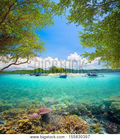 Beautiful coral reef in the background of a tropical desert island Gili Bedis and green mountains. Lombok Island Indonesia.