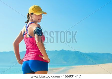 Fitness runner woman in cap wearing phone armband and headphones on beach background and mountains.