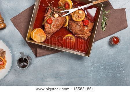 Beef meat stew. Top view braised beef meat stew with tomatoes lemon garlic and rosemary in pot
