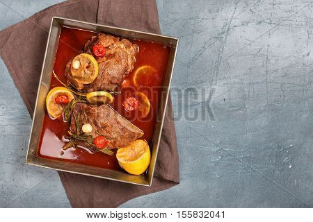 Beef meat stew. Top view with braised beef meat stew with tomatoes lemon garlic and rosemary in pot. Copy space