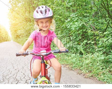 Happy Child Riding A Bike In Outdoor.
