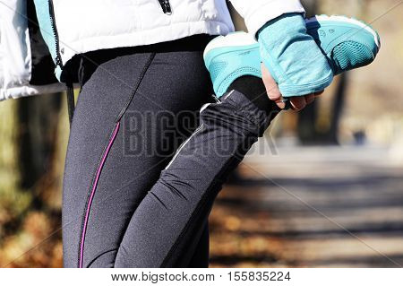 young runner woman stretching in the autumn forest  before run