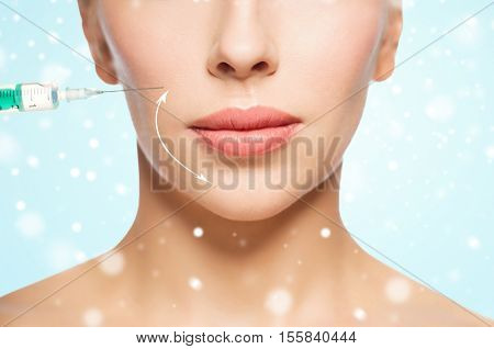 people, cosmetology, plastic surgery, anti-aging and beauty concept - close up of beautiful young woman face with lifting arrow and syringe making injection over blue background and snow