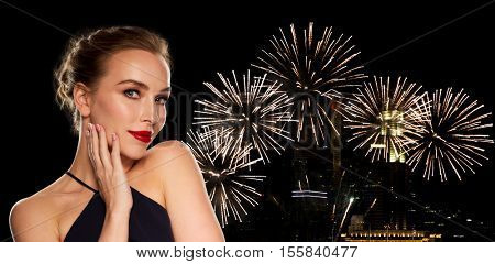 people, luxury, holidays, new year and fashion concept - beautiful woman in black with red lips over night city firework lights background