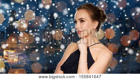people, luxury, jewelry, christmas and holidays concept - beautiful woman in black wearing diamond earrings and bracelet over night singapore city lights background and snow