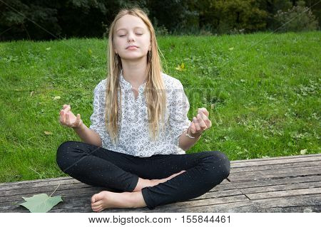 Front Portrait Of Blond Young Girl Practicing Yoga On A Sunny Day