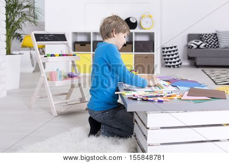 Focused Young Boy Is Sitting At Table
