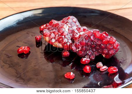 Carmine Pomegranate fruit cut dissect on black dish