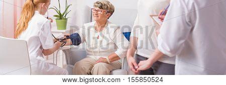 Nurse Taking Blood Pressure Of A Senior Woman