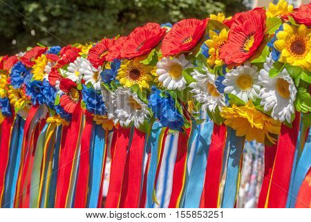 multicolor artificial flowers, wreath fashion made of fabric, many Ukrainian national women's headdresses wreaths hang in a row, selective focus