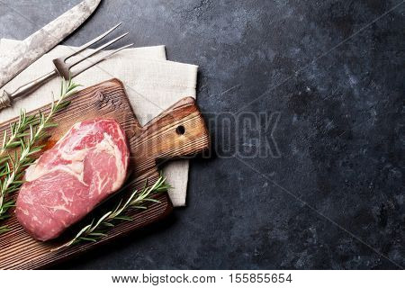 Raw beef steak cooking and ingredients. Meat piece, herbs and spices. Top view with copy space over stone table
