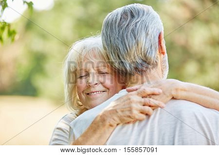 Old woman hugging an old man in the nature in summer