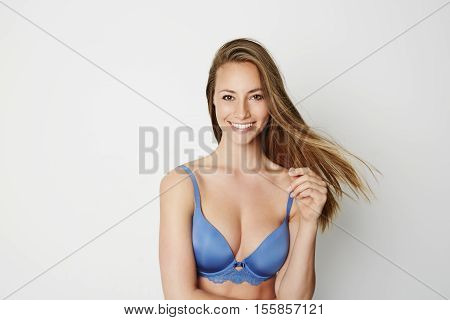 Beautiful woman in blue bra with windy hair smiling