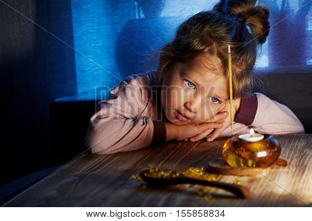 A little girl of 3 children looking at something like a lit candle in a candlestick. Home warmth and comfort as a child