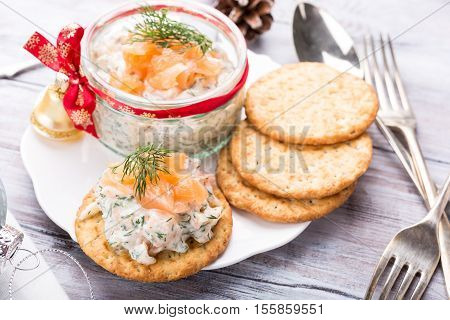 Smoked salmon, soft cheese and dill spread, mousse, pate, rillette in a jar with crackers on white wooden background. Delicious Christmas themed dinner table. Holiday concept. poster