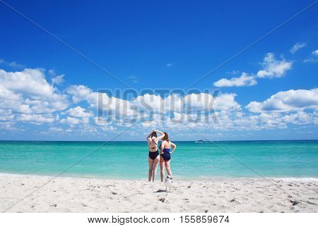MIAMI BEACH, UNITED STATES - FEBRUARY 12: People walk and relax at the sunny South Beach of Miami near Atlantic Ocean on 12th of February, 2016 in Miami Beach.