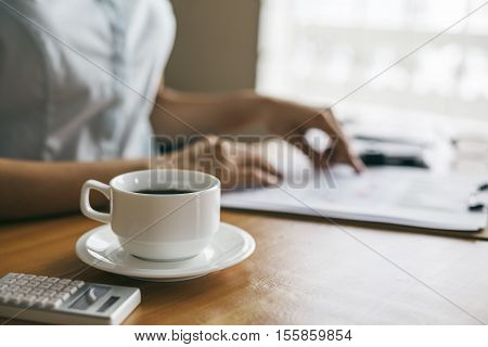 businesswoman indoor reading document on her desk