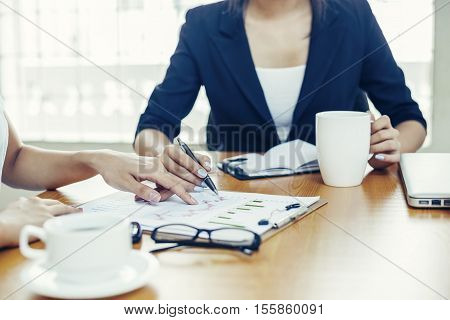 two businesswomen discussing on analysis chart and drinking coffee