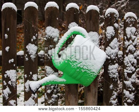 first snow.green watering can on the fence in the garden under the snow