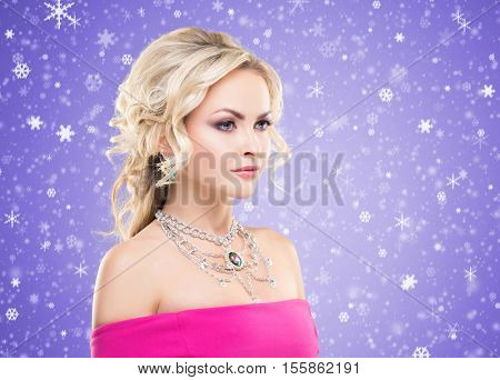 Beautiful blond girl with luxury golden necklace over magenta winter background. Christmas concept.