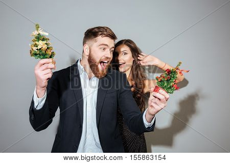 Attractive joyful couple in smart wear having christmas party over gray background