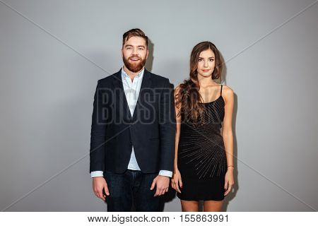 Handsome man in smart suit and attractive woman in black dress standing and looking at camera over gray background