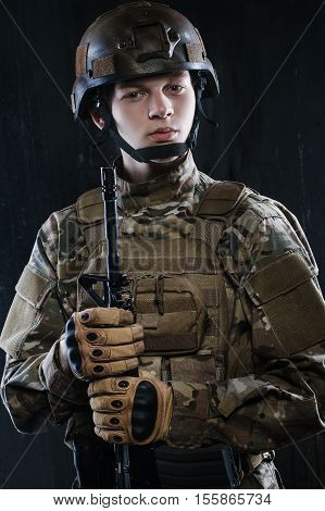 Portrait of a young soldier in the ammunition and a rifle in his hands. Around the world those guys keep us safe