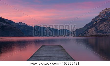 Spectacular sunset over lake in the mountains. Gorgeous colors of clouds reflected in water. long exposure