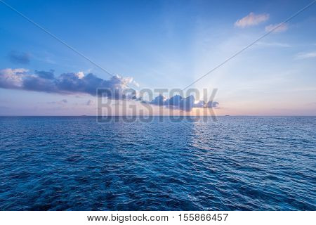 Sunset over ocean. On the horizon the sun's rays shine through the clouds