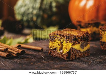 Pumpkin chocolate brownie on a dark wooden background. Baking for Thanksgiving Day. Selective focus. Toned image