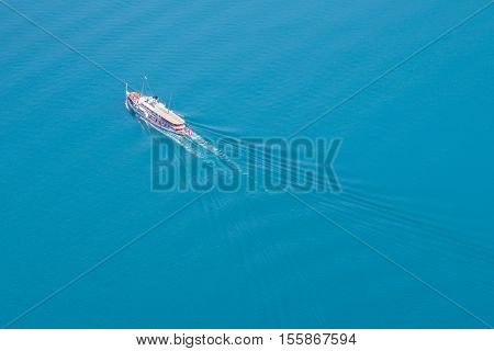 Steamship sails with tourists on the lake and leaves a trail of ripples on the water. View from above