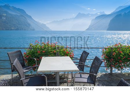 On the shore of lake a small cafe table and chairs. Flowers hanging on the railing. Silhouettes of mountains in the distance. Autumn day sun and blue sky.