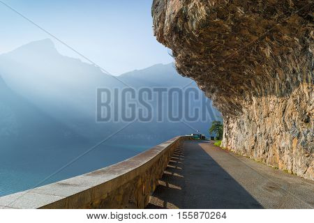 Road along the edge of the cliffs along the lake. Mountain stones hanging from above and secure with a grid. Rays of the sun creates volumetric perspective