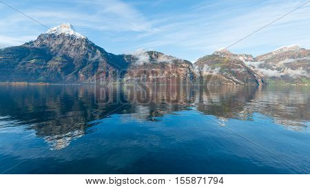 White light clouds over the mountains. Reflection of sky mountains and clouds in lake water. Autumn foliage painted in orange. Kanton Uri