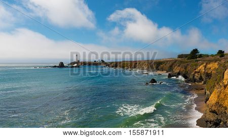 California coast. Famous lighthouse on a rock. Ocean waves wash the beach. Clouds on the blue sky.