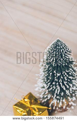 christmas tree and gift on wood.
